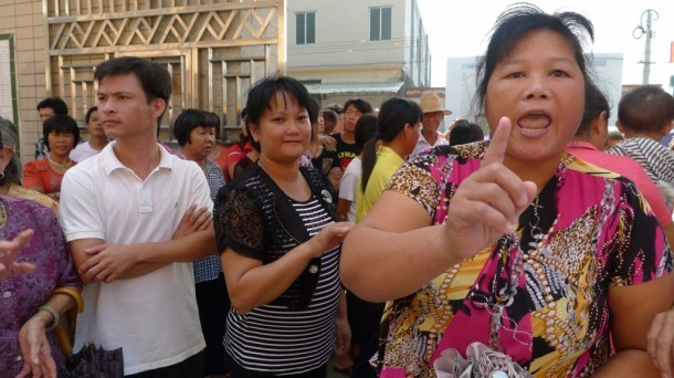 wukan-the-flame-of-democracy-2013-001-woman-making-point-to-camera-in-crowd