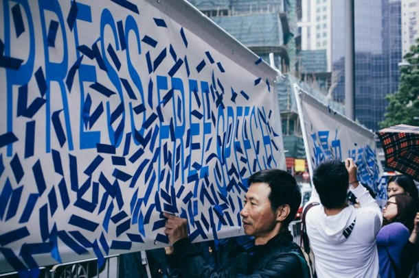 Protestors paste blue ribbons on banners to be presented to Kevin Lau, an editor who was seriously wounded in an attack. Photo: Kevin Yeoh