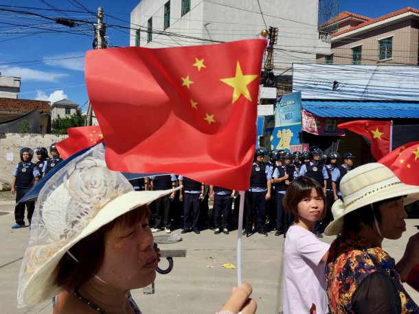 Protestors in Wukan march past hundreds of armed police